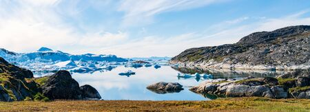 Greenland arctic nature landscape with icebergs in Ilulissat icefjord. Panoramic banner photo of scenery ice and iceberg in Greenland in summer.