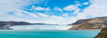 Panoramic view of glacier in Greenland. Glacier front of Eqi glacier in West Greenland AKA Ilulissat and Jakobshavn Glacier. Heavlly affected by Climate Change and Global Warming.
