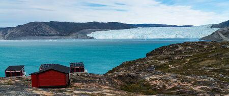 Greenland glacier nature landscape with famous Eqi glacier and lodge cabins. Tourist destination Eqi glacier in West Greenland AKA Ilulissat and Jakobshavn Glacier. Heavlly affected by Global Warming.