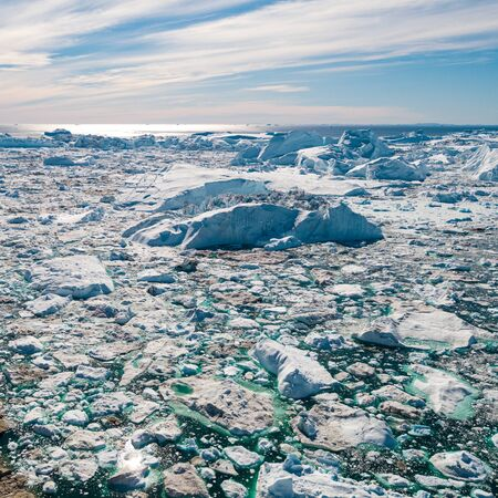 Iceberg and ice from glacier in arctic nature landscape on Greenland. Aerial photo drone photo of icebergs in Ilulissat icefjord. Affected by climate change and global warming. Stock fotó