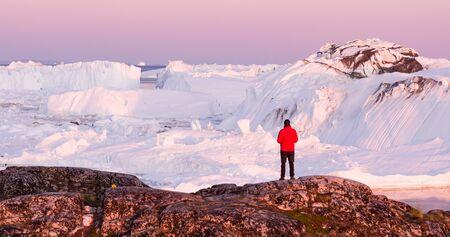 Réchauffement climatique - Paysage d'icebergs du Groenland du fjord glacé d'Ilulissat avec des icebergs géants. Icebergs de la fonte des glaciers. La nature arctique fortement affectée par le changement climatique. Touriste de personne regardant la vue