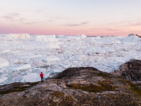 Travel in arctic landscape nature with icebergs - Greenland tourist man explorer - tourist person looking at amazing view of Greenland icefjord - aerial drone image. Man by ice and iceberg, Ilulissat. Stock Photo