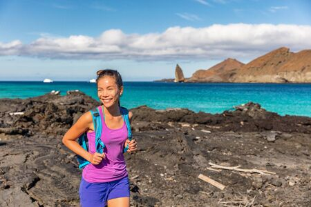 Galapagos tourist walking on Santiago Island in Galapagos Islands. Pinnacle Rock and Bartolome Island in background. Famous Galapagos cruise ship tour destination. 스톡 콘텐츠