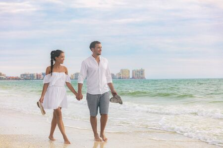 Beach couple romantic sunset walk Asian woman and Caucasian man relaxing walking on Florida vacation beach travel holidays wearing white dress and linen clothes. Happy interracial relationship. Imagens