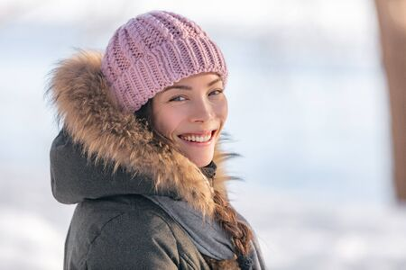 Winter woman portrait in cold outdoor nature. Asian girl model wearing wool hat and fur jacket outside in winter background, natural beauty.