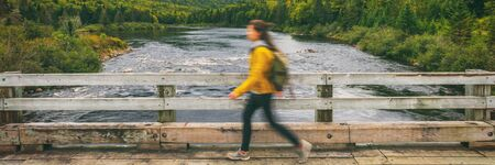 Hiker woman with backpack crossing river walking on bridge. Motion blur of tourist traveling in outdoor nature landscape fall autumn background panorama banner. Quebec, Canada.