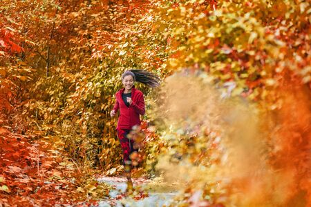 Autumn fall foliage runner woman running in forest woods with beautiful colors in tree leaves nature background. Trail run athlete Asian girl happy training outdoors. Banco de Imagens