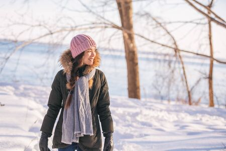 Winter woman walking out on forest walk in cold outdoor nature river outside. Happy asian girl model wearing wool hat, scarf and fur jacket outerwear enjoying outdoors winter background.