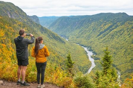 Nature trek hike couple tourists people taking pictures with phone at view of mountain landscape in Autumn forest Canada travel, Jacques Cartier National Park, boreal forest background. Banco de Imagens