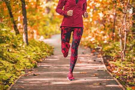 Run path woman running in forest park nature outdoors fitness workout on boardwalk in autumn fall foliage wearing red activewear outfit clothing. Girl athlete jogging outdoor.