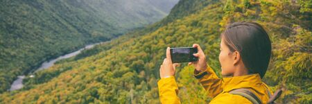 Travel hike woman hiker taking photo with phone of landscape of trail hiking in Quebec autumn foliage background panoramic banner. Canada fall camping lifestyle. Banco de Imagens