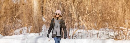 Winter walk happy woman walking on outdoor activity relaxing leisure active lifestyle in forest landscape outside banner panorama. Girl wearing winter coat and hat, scarf, gloves, sunglasses. Banco de Imagens