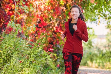 Healthy active lifestyle running Asian young woman training cardio on city park run jogging outdoor in autumn leaves.