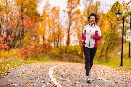 Reife asiatische Frau, die in ihren 50ern aktiv ist. Frauen mittleren Alters, die im Freien einen gesunden Lebensstil im schönen Herbststadtpark in buntem Herbstlaub joggen. Asiatischer chinesischer Erwachsener in den Fünfzigern.