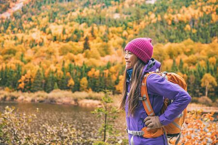 Fall autumn hiker girl outdoor at nature forest lake with backpack for camping travel trip. Happy Asian woman hiking outdoors with bag and hat, cold outerwear gear. Stockfoto