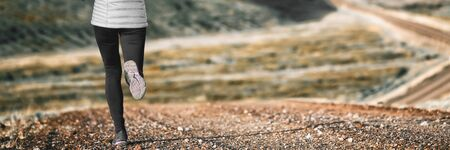Trail runner athlete girl running in winter outdoors with warm tights and running shoes. Banner panorama of legs. Healthy active lifestyle.