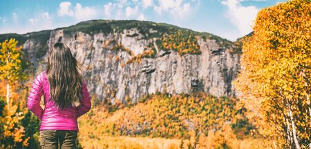 Hike travel autumn hiker woman walking camping in Quebec Canada forest outdoors with mountain background. Hiking girl wearing pink down jacket for fall season scenic landscape banner.