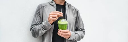 Green juice detox drink healthy man drinking green smoothie cup protein shake panoramic banner. Vegan meal replacement diet at cafe. Spinach morning breakfast panorama. Healthy eating lifestyle. Banco de Imagens