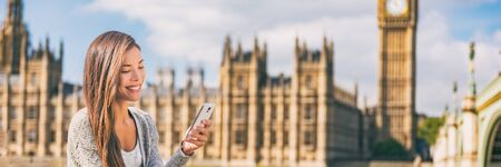 Phone london Asian young woman using cellphone texting on online app on Europe travel city lifestyle banner panorama background. Banco de Imagens