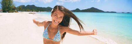 Happy beach vacation woman having fun free with open arms dancing on Caribbean tropical landscape winter travel destination panoramic banner. Asian tourist. Banco de Imagens