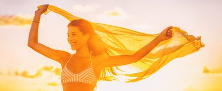 Happy Asian woman free in summer sunset glow feeling good carefree outside banner panorama. Yellow sunshine flare wellness person with scar. Stockfoto