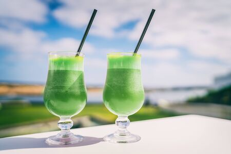 Green smoothies detox Healthy eating juice cleanse juices at cafe. Vegetarian diet juicing trend. Two glasses of spinach vegetable juice on outdoor restaurant table on summer background. Banco de Imagens