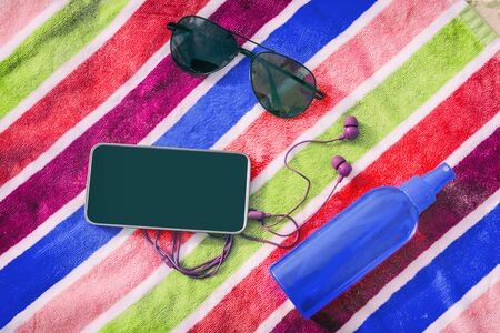 Beach accessories for summer travel holidays. Top view of black screen mobile phone for copy space, earbuds, sunglasses, sun tanning lotion oil, beach towel background.