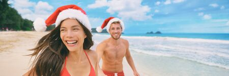 Christmas beach vacation couple on tropical Caribbean holiday in red Santa hats panoramic banner tourists happy on New Year winter vacation.