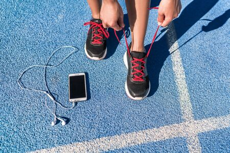 Running motivation music on mobile phone runner woman tying shoe laces. Shoes and feet closeup, athlete getting ready for race or workout on run track with smartphone and earphones. Banco de Imagens