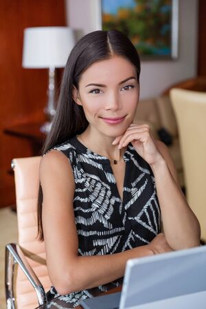 Asian businesswoman working from home. Young business start-up entrepreneur or confident freelancer worker sitting at desk. Portrait of multiracial chinese woman in her 30s.