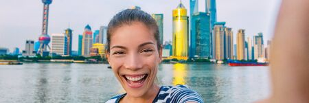 China travel selfie Asian tourist woman talking happy panorama banner landscape. Smiling young girl taking picture with phone of herself in front of Shanghais skyline of skycrapers. Banco de Imagens