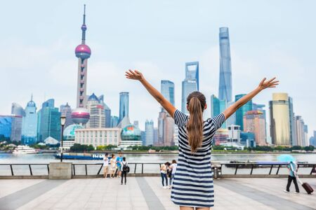 Happy success person with arms up against Shanghai skyline on The Bund. China travel concept or urban lifestyle. Happiness healthy living people in modern city. Woman winning goal challenge. Banco de Imagens