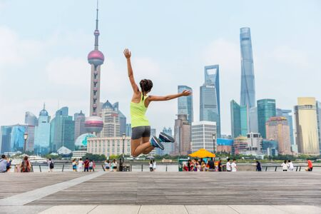 Happy fitness woman jumping of joy and success in Shanghai skyline in goal achievement challenge. Life goals. Weight loss or exercise winning concept.