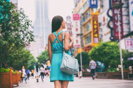 Shanghai city travel lifestyle shopping woman walking on Nanjing Road shop street, China, Asia. Asian girl with purse on urban adventure, famous chinese attraction landmark. Banco de Imagens