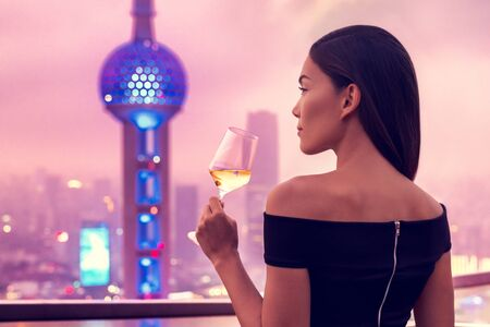 Elegant asian woman in gown drinking white wine glass at rooftop bar terrace looking at city lights skyline view of Shanghai in sunset. Luxury travel or high end lifestyle. Banco de Imagens