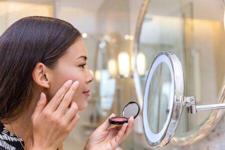 Mujer joven asiática poniendo crema de rubor con los dedos mientras mira en el espejo de maquillaje en casa en el baño. Rutina matutina de niña maquillándose antes de ir a trabajar. Cuidado de la piel facial.
