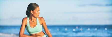 Healthy fit active Asian woman looking to the side outdoor beach background panoramic banner. Yoga girl in sports bra stretching at sunset.