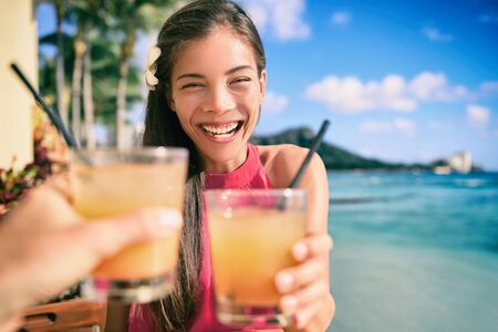 Cocktail toast couple going out on beach restaurant cheering with rum mai tai drinks on Waikiki, Honolulu, Hawaii travel. Happy Asian woman holding glass of alcohol toasting with man. Фото со стока