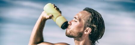 Athlete drinking water bottle during intense training workout sweating in summer heat. Man runner thirst quenching hydration sports bottle drink panoramic banner.