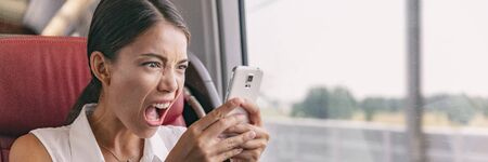 Angry crazy Asian woman upset at mobile phone problem not working or texting upset to somebody over smartphone 5g internet during work commute train ride panoramic banner.