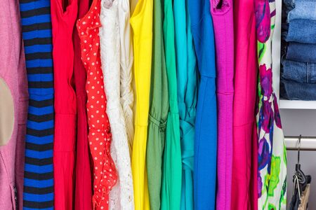 Clothing closet many colors dresses, variety of fabric and patterns for summer fashion style. Womens clothes in pink, red, green, blue dress, with stripes, lace, polka dots. Cute outfits.