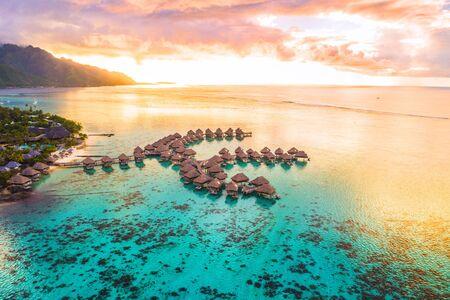 Antenne de vacances de voyage de luxe de la station balnéaire de bungalows sur pilotis dans l'océan du lagon des récifs coralliens par la plage. Vue d'en haut au coucher du soleil de l'escapade paradisiaque Moorea, Polynésie française, Tahiti, océan Pacifique Sud.