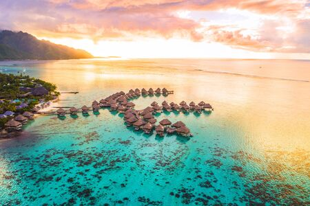 Luxury travel vacation aerial of overwater bungalows resort in coral reef lagoon ocean by beach. View from above at sunset of paradise getaway Moorea, French Polynesia, Tahiti, South Pacific Ocean. Stok Fotoğraf