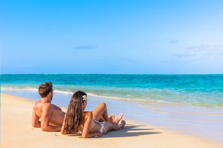 Couple on beach travel honeymoon vacation lying down sunbathing relaxing on luxury holiday in idyllic destination. Young tourists in love. Stok Fotoğraf