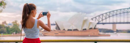Australia Sydney travel tourist woman at Opera House panoramic banner landscape crop. Asian girl taking photos with mobile phone during summer vacation trip. 免版税图像