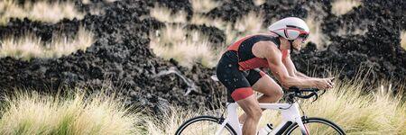 Biking triathlete man cycling road bike under the rain during triathlon race in Hawaii nature landscape. Sport athlete training endurance workout extreme weather banner panoramic. Stok Fotoğraf
