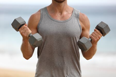 Fitness man training biceps lifting dumbbells doing bicep curl arm exercise workout exercising arms with two heavy dumbbell weights. Free weight exercises for bigger muscles.