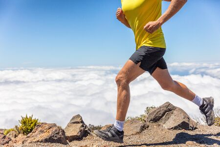 Trail running man runner legs and shoes training on mountain outdoors. Nature landscape. Sport fitness male athlete