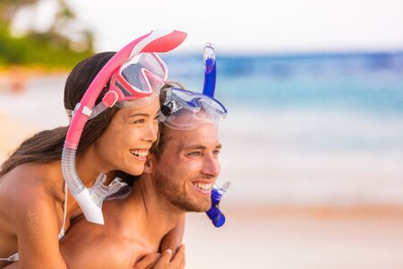 Happy travel beach snorkeling couple enjoying summer holidays vacation fun. Multiracial people together in love with diving masks, sports leisure activity for vacations.