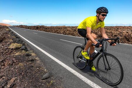 Road bike cyclist man biking riding racing bicycle training for triathlon race. Sports athlete biking on road working out cardio living active and healthy lifestyle.